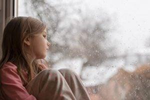 비 내리는 창밖을 내다보고 있는 여자 아이