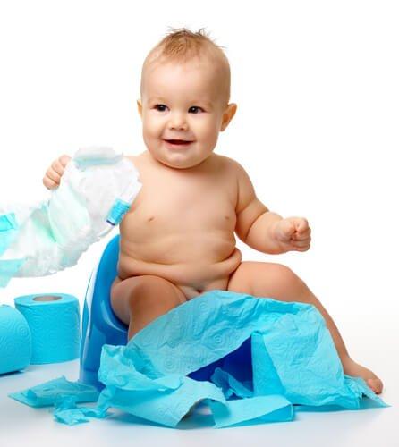 기저귀를 들고 아기 변기에 앉아 있는 아기